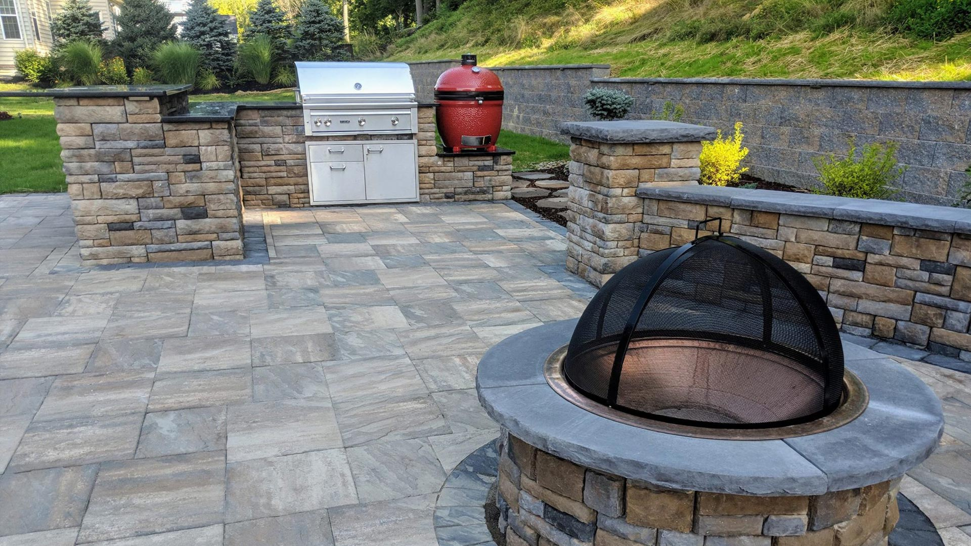 Custom outdoor kitchen with a patio, fire pit, seating wall, and retaining wall at a home in McMurray, PA.