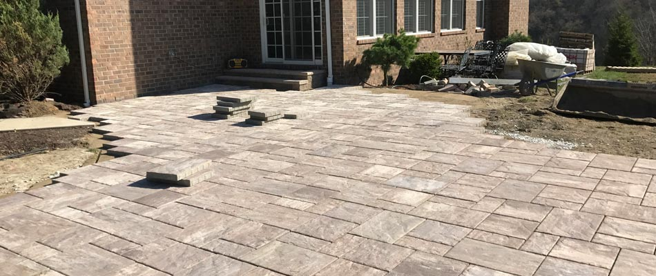 The custom patio and walkway perfectly complements this McMurray brick home.