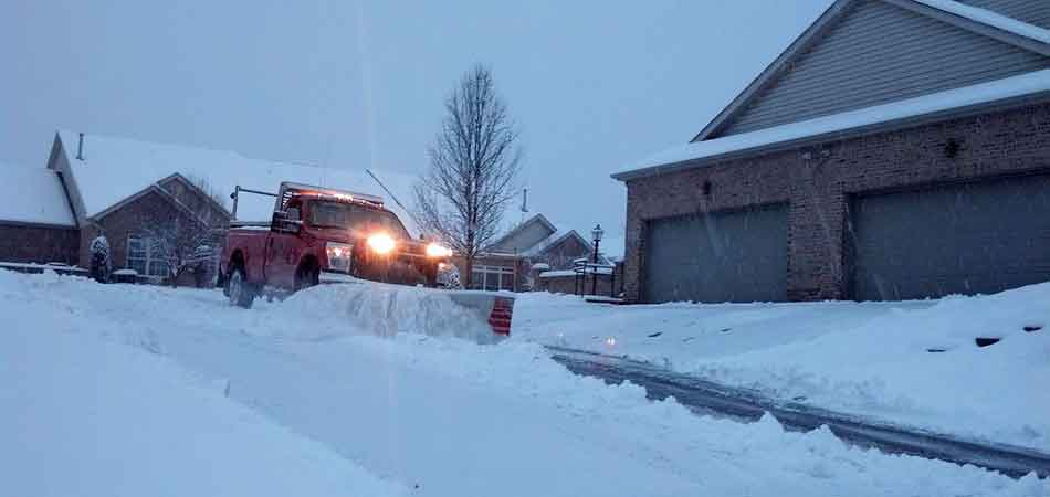 One of our M.J. Donas Landscaping team members plowing snow on a private road.