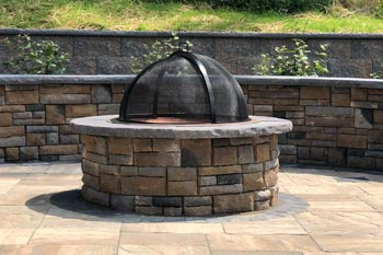 Custom built fire pit with a seating wall recently installed at a residential property in Venetia, PA.